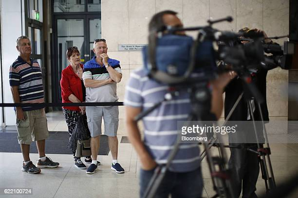 People look at an electronic board displaying stock information not pictured inside the Australian Securities Exchange operated by ASX Ltd in Sydney...