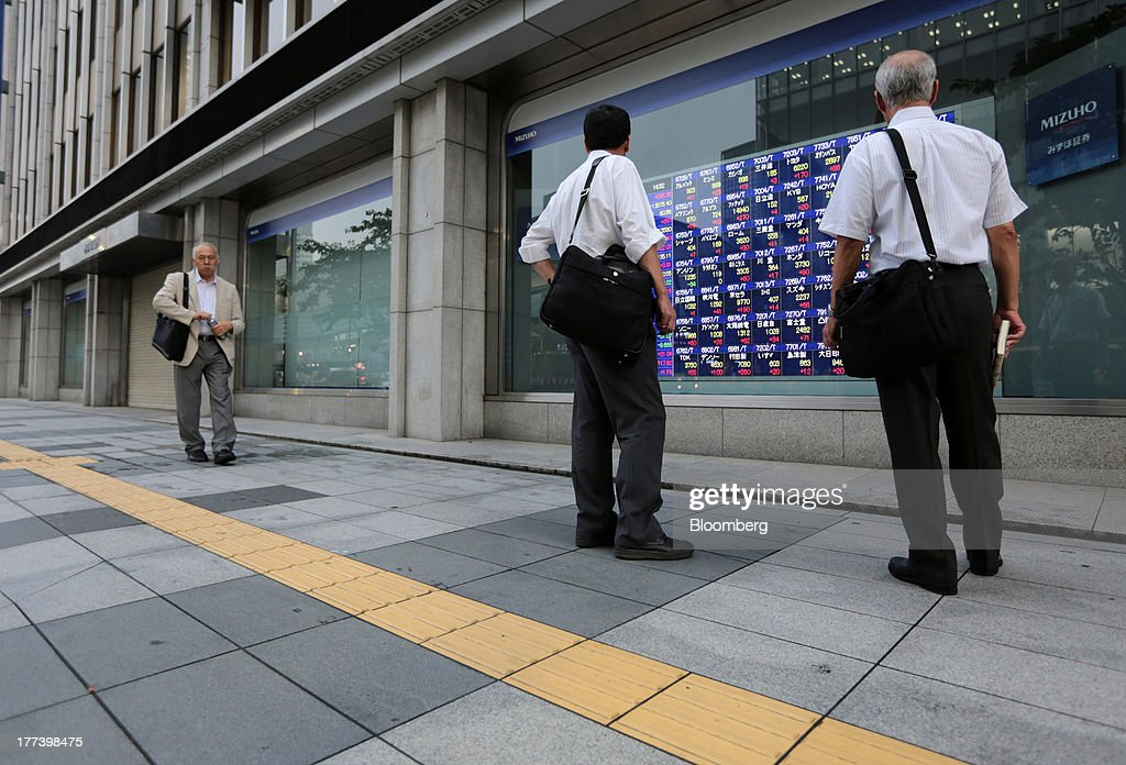 People look at an electronic stock board outside a securities firm in Tokyo, Japan, on Friday, Aug. 23, 2013. Japanese shares rose, with the Topix index halting three days of losses, as exporters advanced after the yen weakened against the dollar. Photographer: Yuriko Nakao/Bloomberg via Getty Images