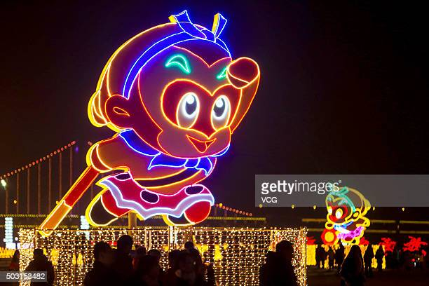 People look at an illuminated monkey lantern during a New Year lantern show on January 1 2016 in Dalian China