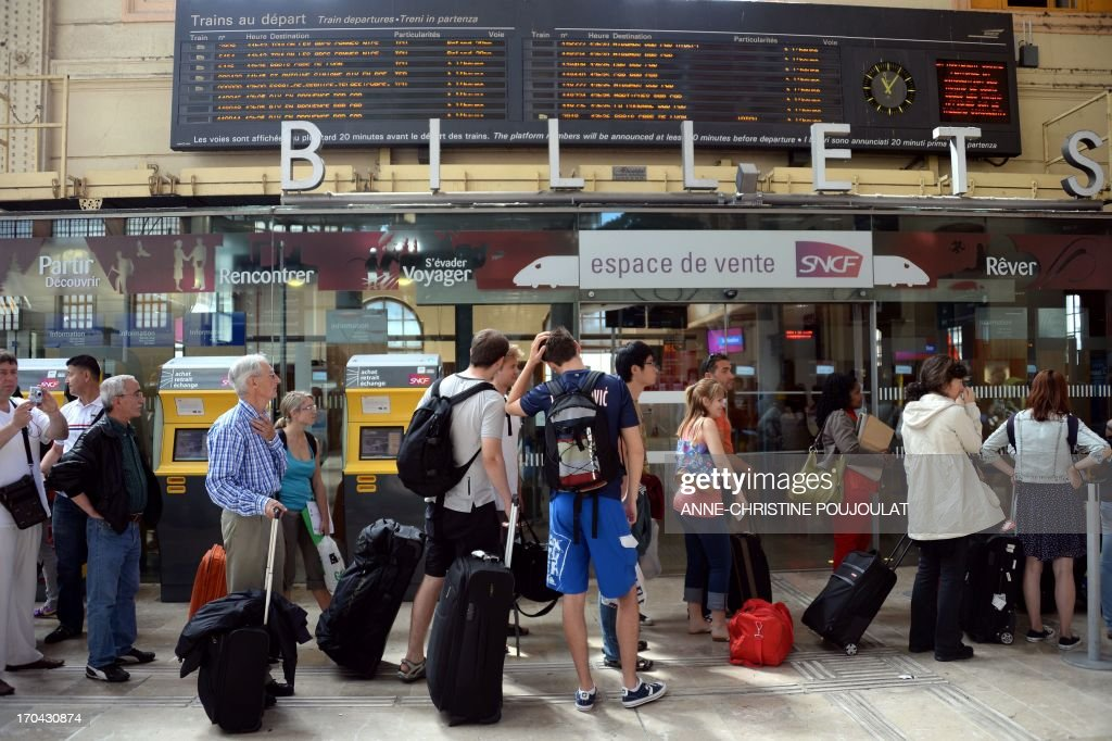 People look at an information board at the Saint Charles train station during a strike by French SNCF state-owned railway company employees on June 13, 2013, in Marseille. The strike was called by unions hostile to reforms of the train services sector recently proposed by the French government.