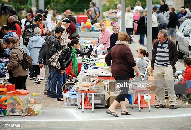 People look at and buy second hand goods on a flea market on September 23 2012 in VillefranchedeLauragais southern France AFP PHOTO REMY GABALDA