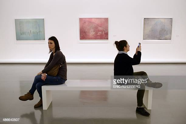 People look at artworks by Lucio Fontana on April 25 at the Modern Art Museum in Paris A retrospective exposition dedicated to the Argentinaborn...