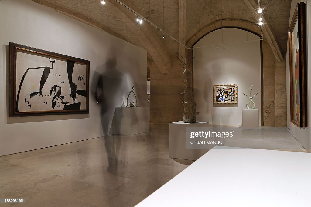 People look at artworks by Spanish artist Joan Miro (1893-1983) during the exhibition 'Miro: the experience of watching' at the Palencia Cathedral in Burgos northern Spain on October 4, 2013. The project, curated by Carmen Belen Fernandez Galan, focuses on works by Miro during the last years of his life when a fundamental change in his creative trajectory is noted. The exhibition will travel to various cities of the US in 2014. AFP PHOTO / CESAR MANSO