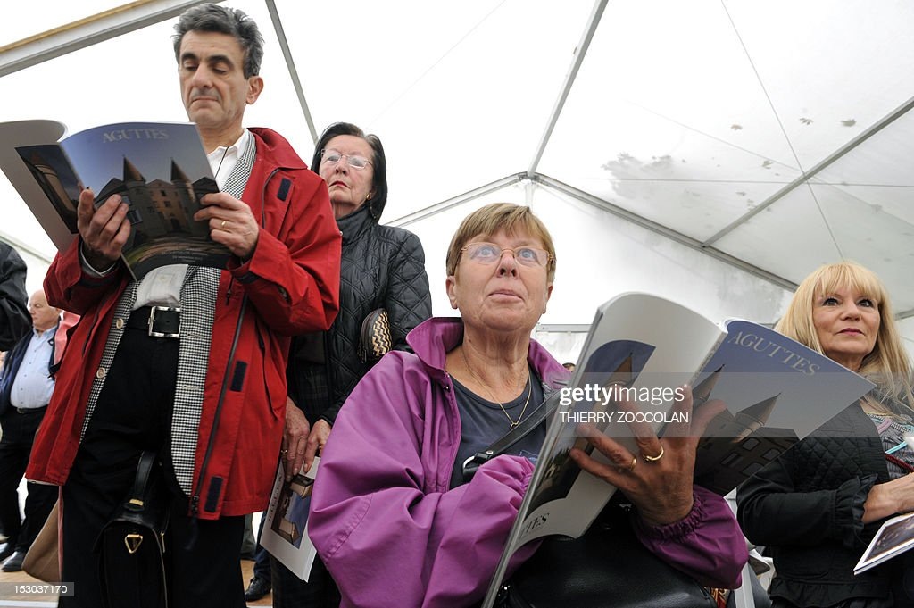 People look at auction brochures as they attend the auction of the furniture of the Chateau de Varvasse (Varvasse castle) belonging to France's former president Valery Giscard d'Estaing, on September 29, 2012 in Chanonat, central France.