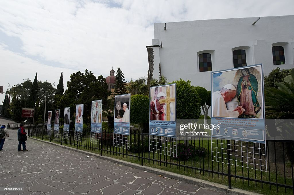 People look at banners with images of Pope Francis on display at 'La Villa' or Basilica de Guadalupe complex where Pope Francis is due to give an open mass-- in Mexico City on February 10, 2016. Pope Francis will visit four Mexican states from next February 12 to 17. AFP PHOTO / YURI CORTEZ / AFP / YURI CORTEZ