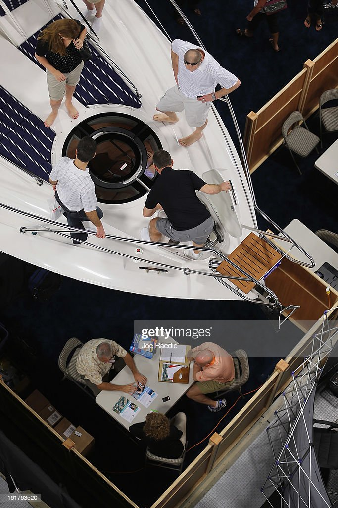 People look at boats on display at The Miami International Boat Show at the Miami Beach Convention Center on February 15, 2013 in Miami Beach, Florida. The boat show has more than 3,000 boats on display and more than 1,000 boating accessories, the show ends on Monday.