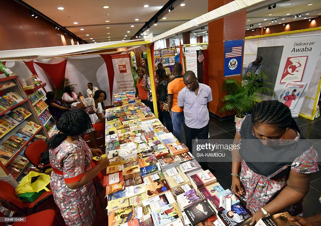 People look at books displayed during the International Book Fair of Abidjan on May 28, 2016. / AFP / SIA
