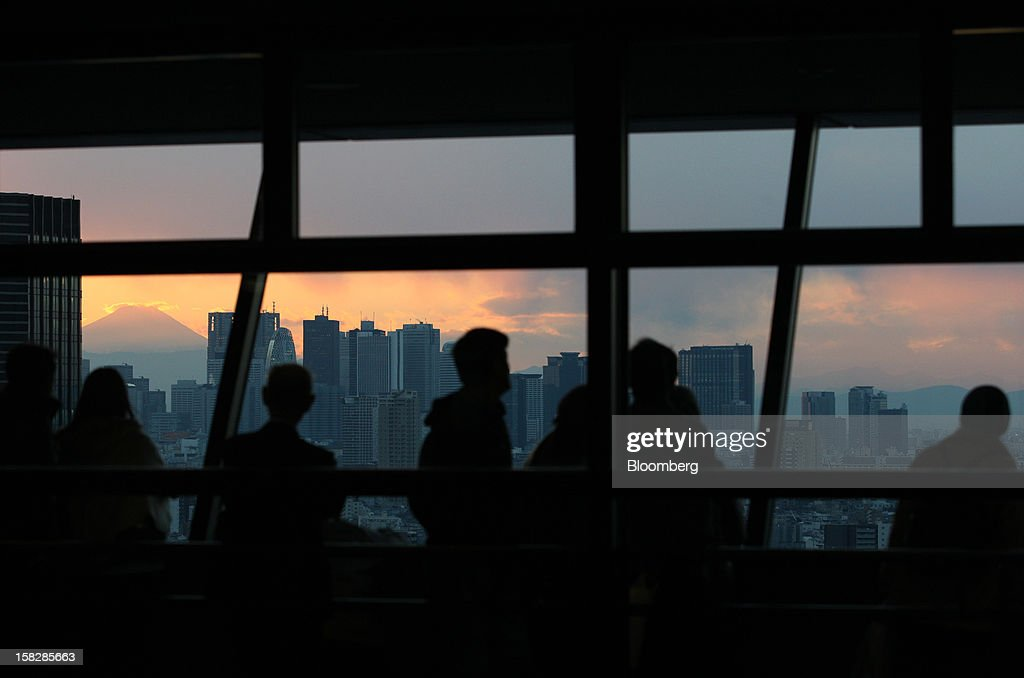People look at buildings in front of Mount Fuji from an observation deck at dusk in Tokyo, Japan, on Wednesday, Dec. 12, 2012. Japan's economy shrank in the last two quarters, meeting the textbook definition of a recession, as the dispute with China, the country's biggest export market, caused consumers there to shun Japanese products and contributed to Japan's worst year for exports since the global recession in 2009. Photographer: Tomohiro Ohsumi/Bloomberg via Getty Images