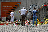 People look at candles and flowers left by mourners at the makeshift memorial to victims of the Love Parade disaster on its fifth anniversary on July...