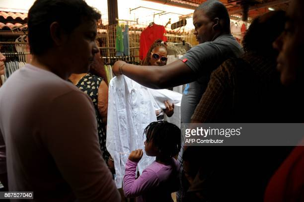 People look at clothes at a market in Havana on October 27 2017 Almost drowned by the crisis of the 90s the emerging Cuban fashion begins to thrive...