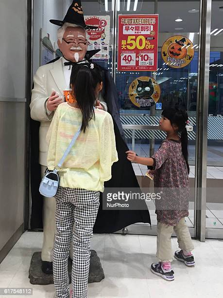 People look at Colonel Sanders of the Halloween version at a Kentucky Fried Chicken restaurant in Tokyo Japan 23 October 2016
