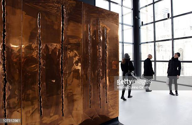 People look at Concetto Spaziale by Lucio Fontana during the Museo Del Novecento press preview on December 3 2010 in Milan Italy