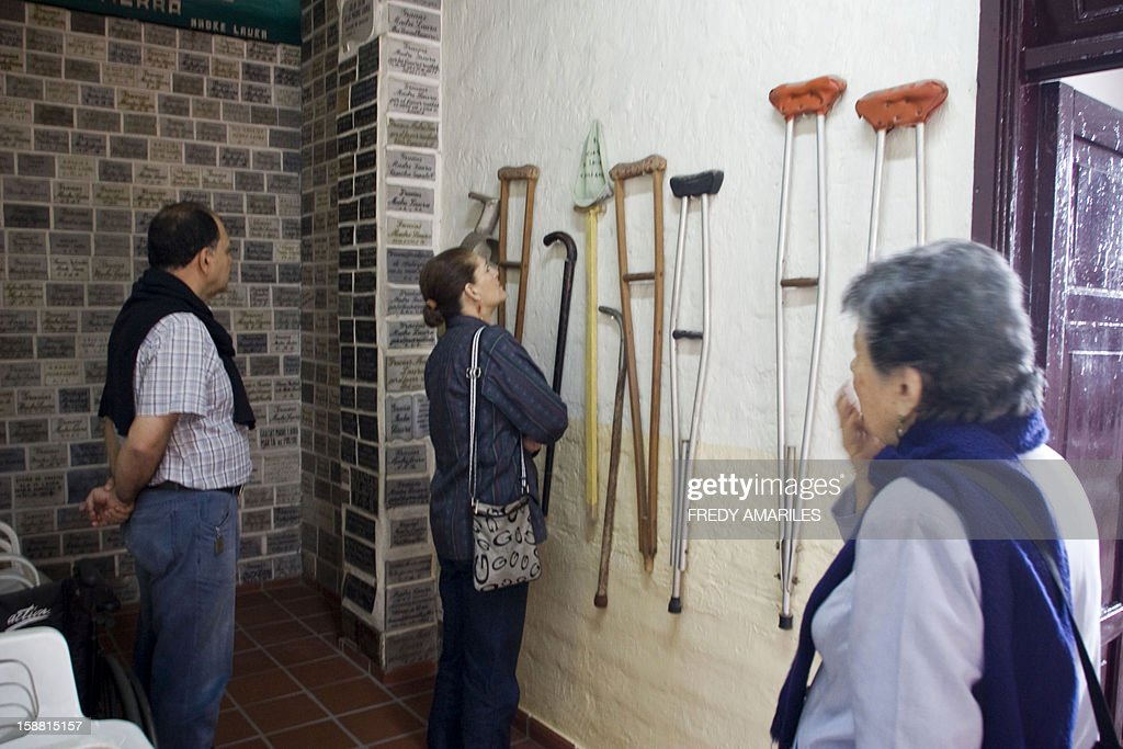 People look at crutches next to thank you plaques for Mother Laura at the convent where she lived in Medellin, Colombia on December 30, 2012. Mother Laura Montoya Upegui died on October 21, 1949, and was declared blessed by Pope John Paul II on April, 2004. On December 20, 2012, Pope Benedict XVI approved her canonization, making her the first Colombian saint, after recognizing a miracle. AFP PHOTO/Fredy AMARILES