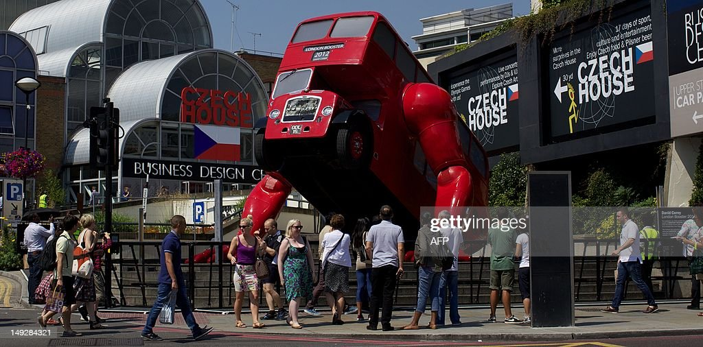 People look at David Cerny's double-decker bus art installation 'London Booster' on July 26, 2012. The Czech artist has adapted a 1957 London bus and added huge mechanical arms which enable it to do press-ups. The work was commissioned by the Czech Olympic Committee, at Czech House.