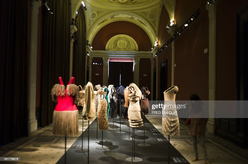 People look at dresses of French designer Azzedine Alaia during his exhibition at the Palais Galliera, on September 25, 2013, in Paris.