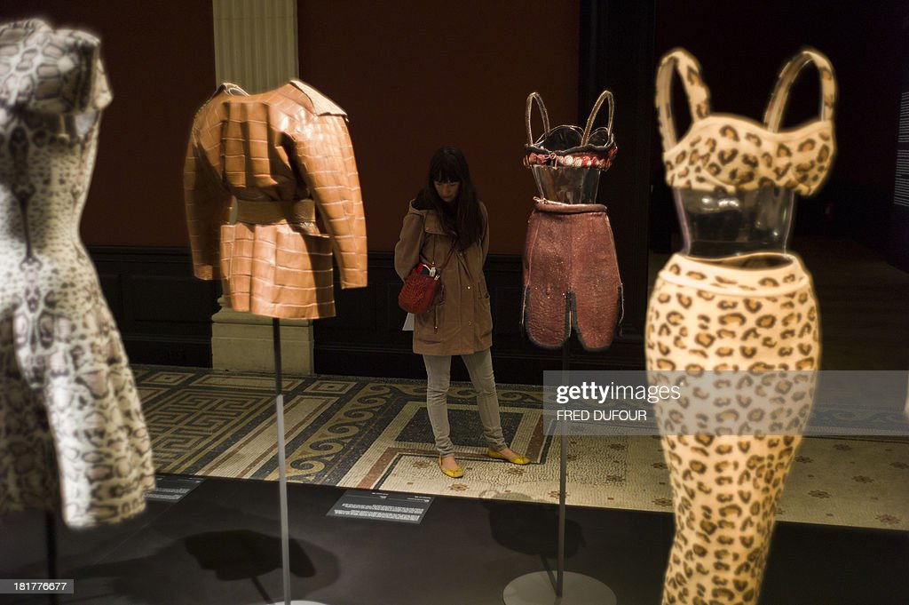 People look at dresses of French designer Azzedine Alaia during his exhibition at the Palais Galliera, on September 25, 2013, in Paris. AFP PHOTO / FRED DUFOUR