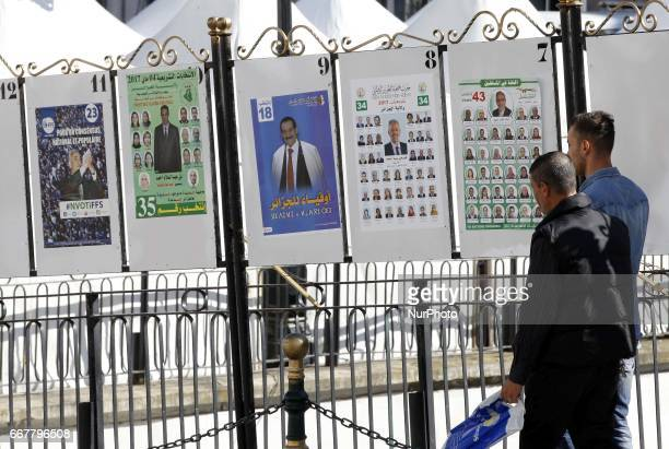 People look at electoral campaign posters for the upcoming legislative elections in Algiers centers Algeria on April 12 2017