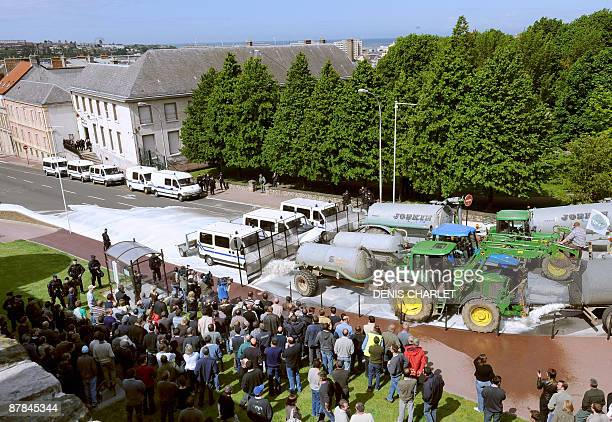 People look at farmers emptying gallons of milk in the streets of BoulognesurMer northern France during a national day of protests of French dairy...