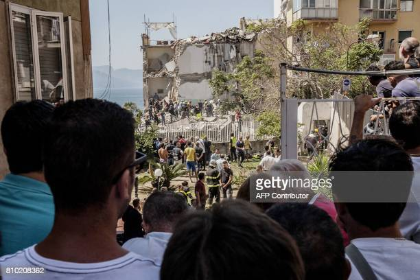 People look at firefighters searching the rubble after two floors collapsed in a small fourstorey building in Torre Annunziata in a town near the...