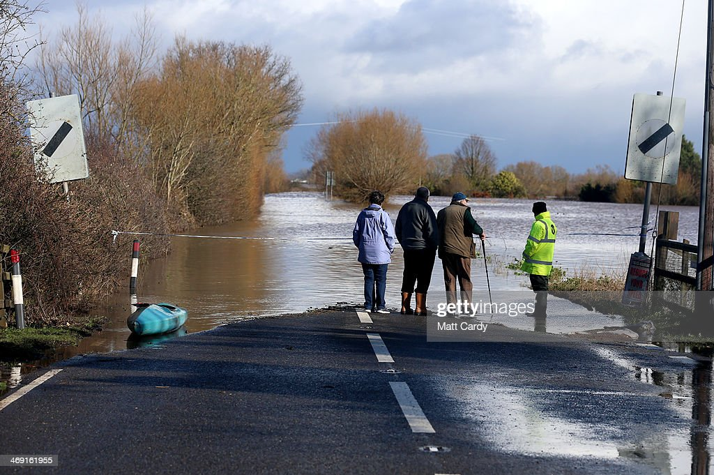 People look at flood waters close to the village of East Lyng that has blocked the main A361 road on February 13, 2014 in Somerset, England. As the Environment Agency continues to issue severe flood warnings for a number of areas on the Somerset Levels, with heavier rains forecast, many people are preparing for the water levels to rise still further.