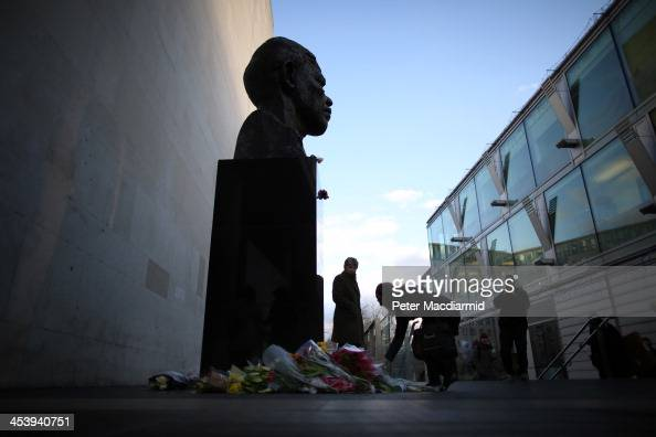 People look at floral tributes placed on a sculpture of Nelson Mandela next to The Royal Festival Hall on December 6 2013 in London England Mandela...