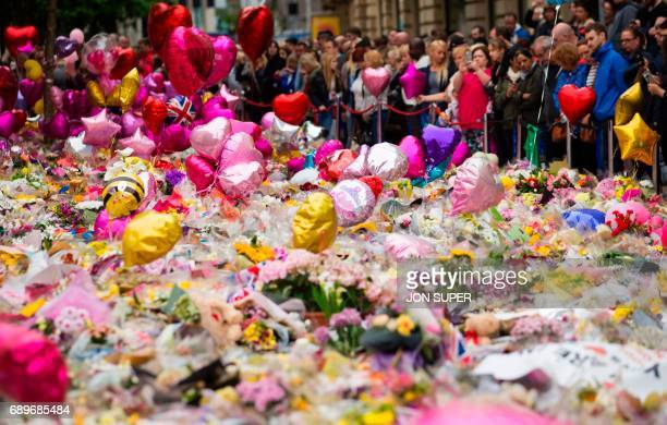 People look at flowers and balloons in St Ann's Square in Manchester northwest England on May 29 placed in tribute to the victims of the May 22...