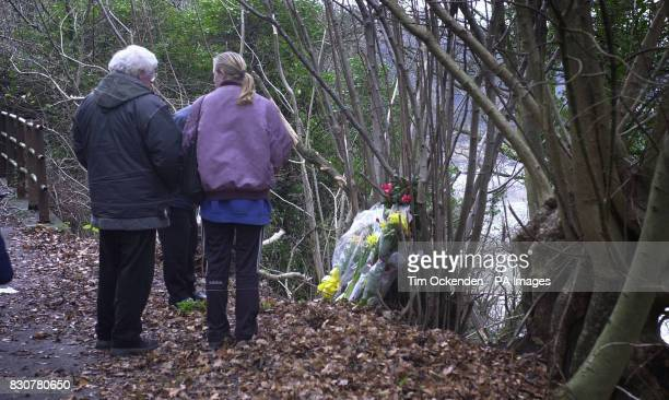 People look at flowers at the scene of the accident in which four people died Sunday evening when the car in which they were travelling left the...