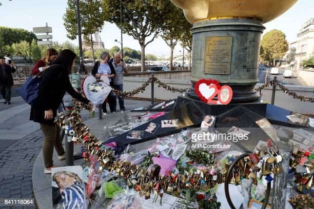 People look at flowers messages and pictures laid around the Flame of Liberty monument which became an unofficial memorial for Diana Princess of...