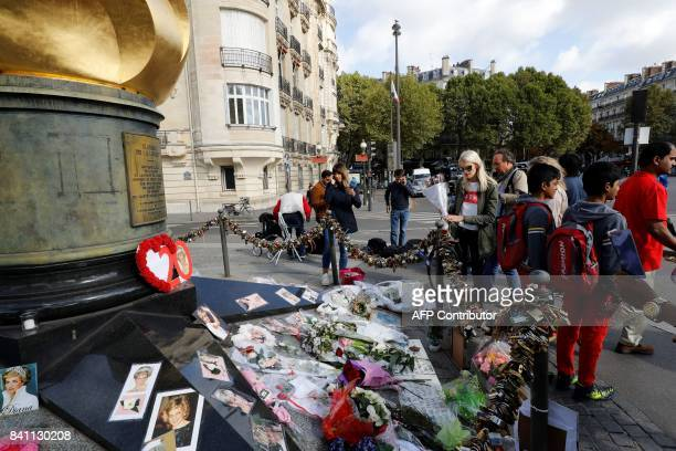 People look at flowers messages pictures and locks laid around the Flame of Liberty monument which became an unofficial memorial for Diana Princess...