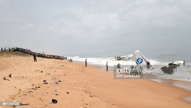 People look at French soldiers trying to pull the wreckage of a cargo plane that crashed off Ivory Coast and killed four people from the sea at the...