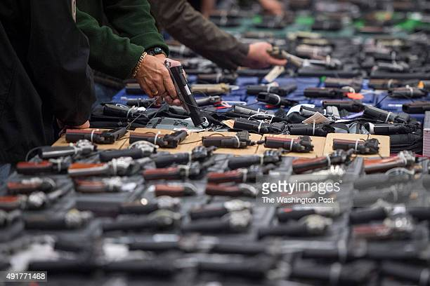 People look at handguns as thousands of customers and hundreds of dealers sell show and buy guns and other items during The Nation's Gun Show at the...