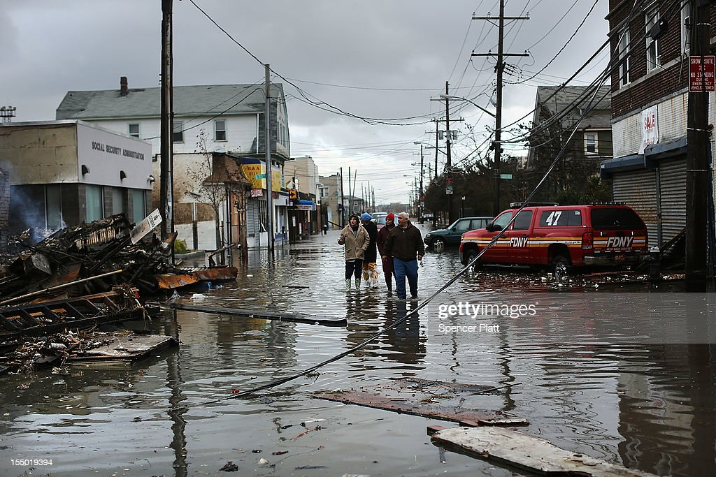 People look at homes and businesses destroyed during Hurricane Sandy on October 30, 2012 in the Rockaway section of the Queens borough of New York City. At least 40 people were reportedly killed in the U.S. by Sandy as millions of people in the eastern United States have awoken to widespread power outages, flooded homes and downed trees. New York City was hit especially hard with wide spread power outages and significant flooding in parts of the city.