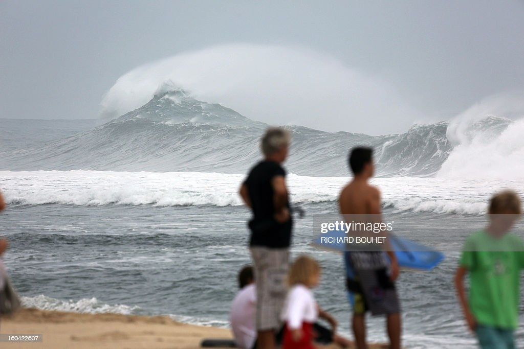 People look at huge waves along the beach of Saint-Gilles on January 31, 2013 on the French Indian Ocean island of La Reunion as the cyclone Felleng was announced at 735 Km north of the island and progresses at the speed of 17 Km per hour. Felleng should approach the coast of the island from 300 km on February 1st.