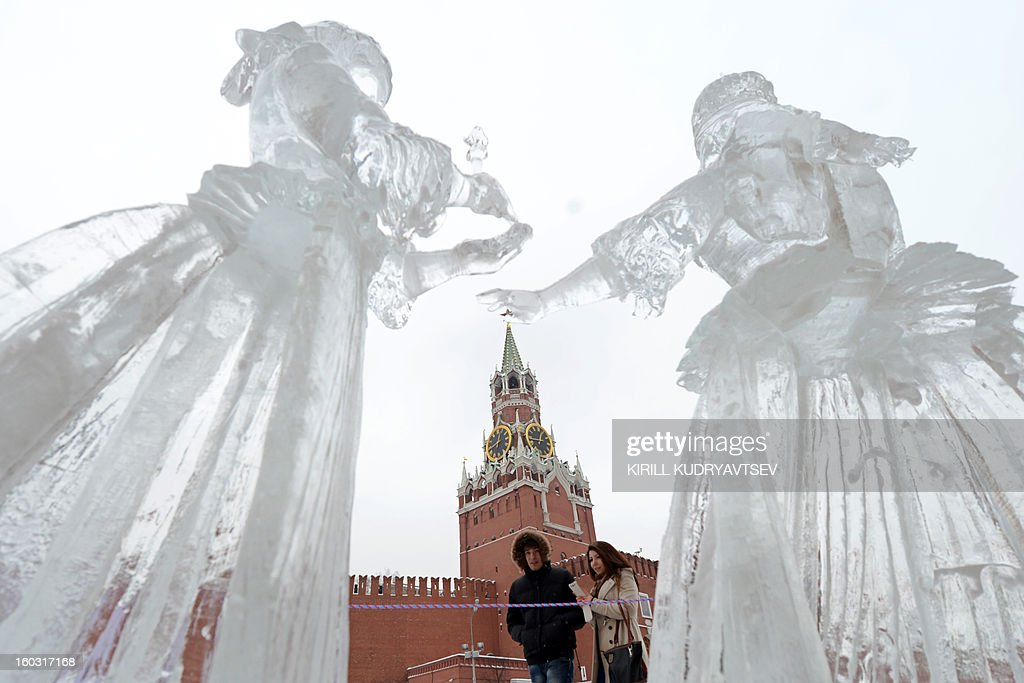 People look at ice sculptures on display near St.Basil's cathedral just outside the Kremlin in Moscow, on January 29, 2013. AFP PHOTO / KIRILL KUDRYAVTSEV