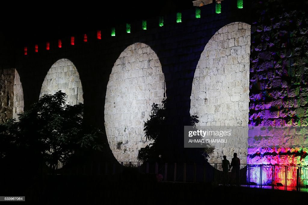 People look at illuminated colors light show projected on the ancient walls of Jerusalem's Old City during the Jerusalem Festival of Lights on May 24, 2016. / AFP / AHMAD