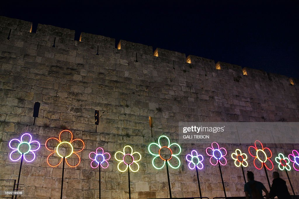 People look at illuminated flowers part of a light show projected on to its ancient walls of Jerusalem's Old City during the Jerusalem Festival of Lights on June 4, 2013.