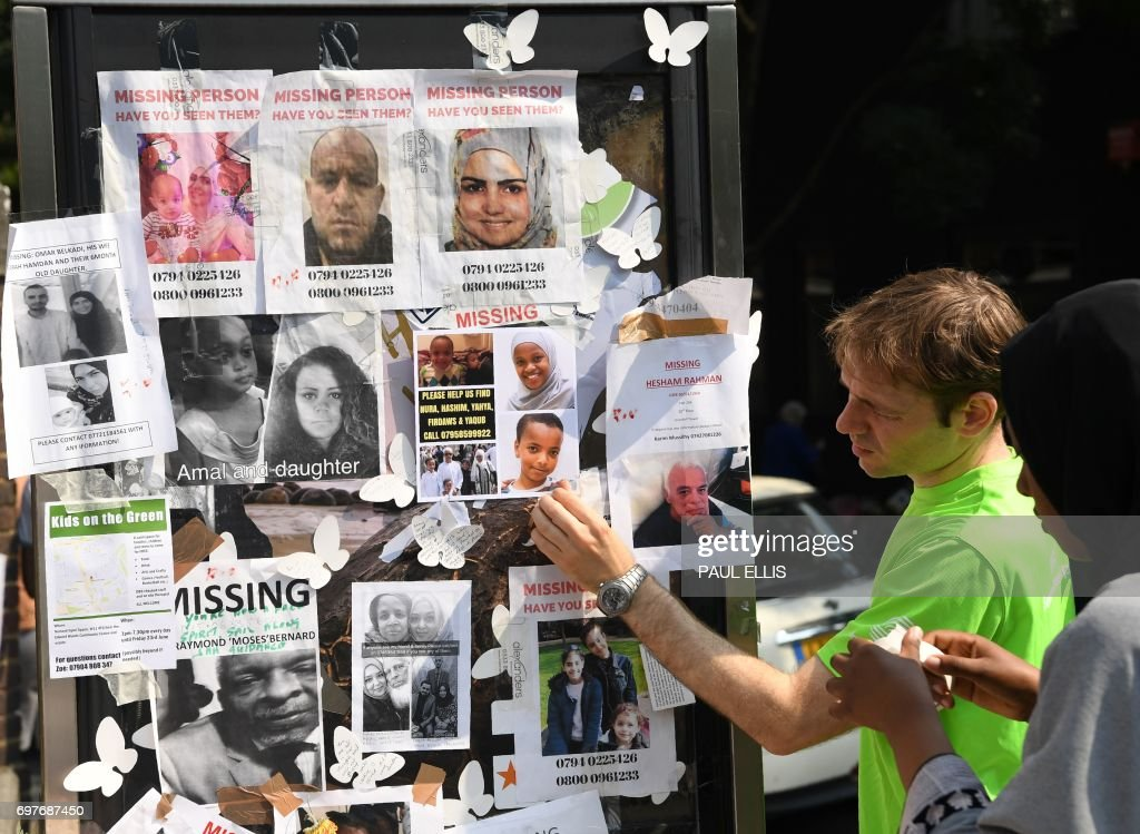 People look at images of missing people, placed on a phone box near to the Grenfell Tower, a residential tower block in Kensington, west London, on June 19, following the June 14 fire which gutted the residential building. Seventy-nine people are dead or missing and presumed dead following a devastating blaze in a London tower block, police said Monday, as Britain held a minute's silence for the victims. / AFP PHOTO / Paul ELLIS