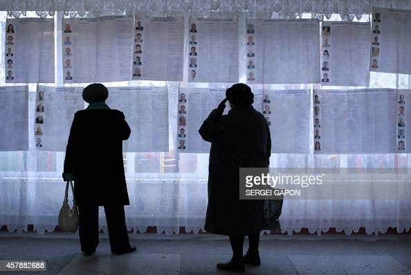 People look at information posters of the candidates for Ukraine's parliamentary elections on voting day in a polling station in Kiev on October 26...