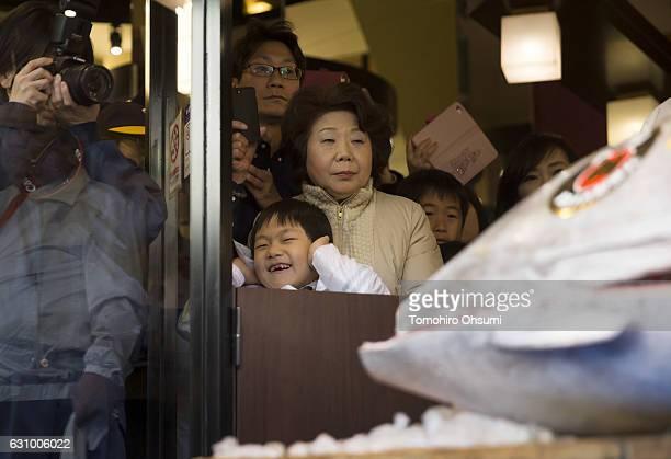 People look at Kiyomura Co President Kiyoshi Kimura not pictured cutting a fresh bluefin tuna in front of one of the company's Sushi Zanmai sushi...