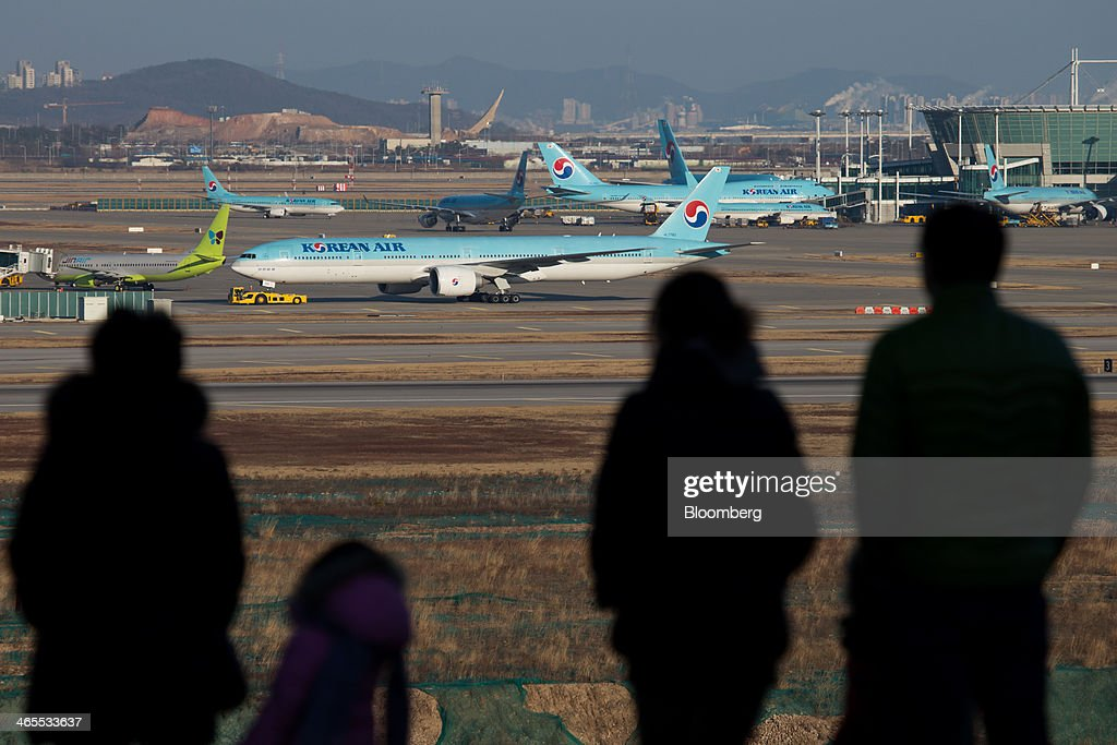 People look at Korean Air Lines Co. passenger aircraft at Incheon International Airport in Incheon, South Korea, on Sunday, Jan. 26, 2014. Korean Air, the nation's biggest carrier, is scheduled to report full-year results on Feb. 3. Photographer: SeongJoon Cho/Bloomberg via Getty Images