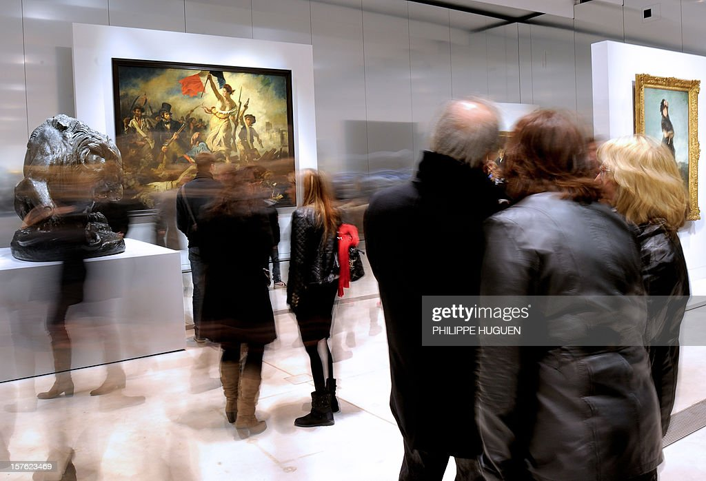 People look at 'La Liberte guidant le peuple' (Liberty Leading the People) by French painter Eugene Delacroix, on December 4, 2012, as they visit the Louvre Museum on the first day of its opening to the public in Lens, northern France. The Louvre museum opened a new satellite branch among the slag heaps of a former mining town Tuesday in a bid to bring high culture and visitors to one of France's poorest areas. Greeted by a group of former miners in overalls and hardhats, President Francois Hollande inaugurated today the Japanese-designed glass and polished-aluminium branch of the Louvre in the northern city of Lens. The 150 million euro ($196 million) project was 60 percent financed by regional authorities in the Nord-Pas-De-Calais region, on the English Channel and the border with Belgium. AFP PHOTO PHILIPPE HUGUEN