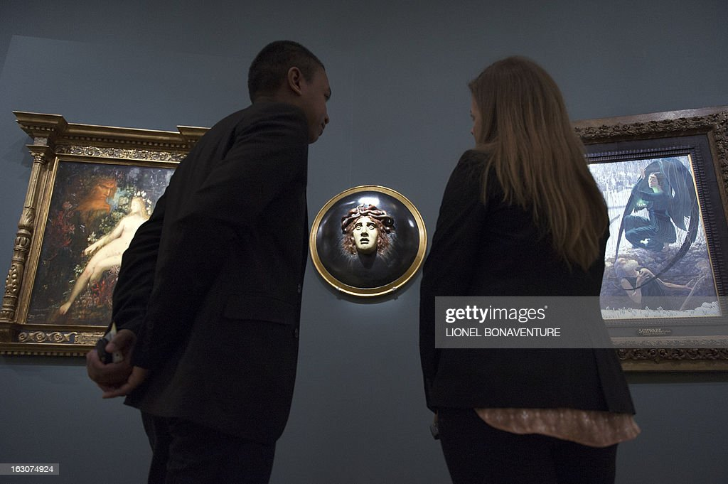 People look at 'La mort et le fossoyeur' by Carlos Schwabe (R) and 'Bouclier avec le visage de meduse' (C) by Arnold Bocklin during the exhibition 'The Angel of the Odd. Dark Romanticism from Goya to Max Ernst' at the Orsay museum in Paris, on March 4, 2013. The exhibition will run from March 5 until June 9, 2013.