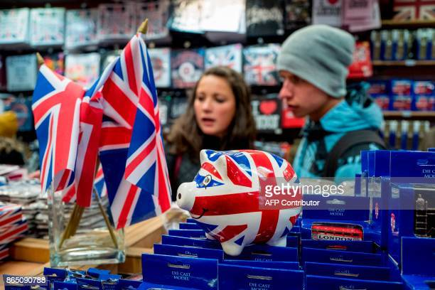 People look at merchandise for sale in a souvenir shop on Whitehall in London on October 22 2017 Britain could be left 'poorer and weaker' by Brexit...