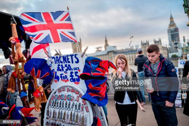 People look at merchandise for sale on a souvenir stall on the south side of the Thames opposite the Palace of Westminster in London on October 22...