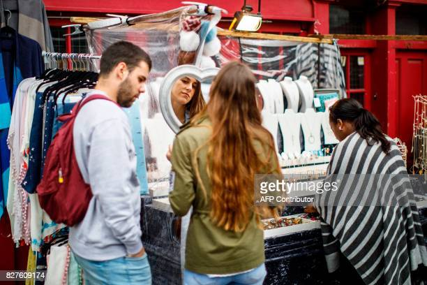 People look at merchandise on a stall at Portobello Road Market in the Notting Hill district of west London on August 8 2017 Last week The Bank of...