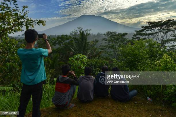 TOPSHOT People look at Mount Agung in Karangasem on the Indonesian resort island of Bali on September 24 2017 Authorities have raised alert levels...