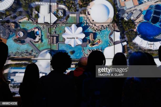 People look at Oceanografic Valencia Aquarium on Google Earth map on a screen as Google Earth unveils the revamped version of the application April...