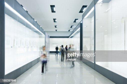 People look at paintings in art gallery