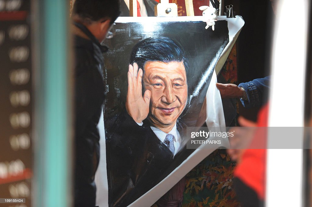 People look at paintings of China's President Xi Jingping in a shop in Shanghai on January 9, 2013. China will overtake the United States economically within six years, the Nation's Health Report issued by the Chinese Academy of Sciences, an official research institute predicts, and go on to become the world's most important country in three decades more, state media said. AFP PHOTO / Peter PARKS