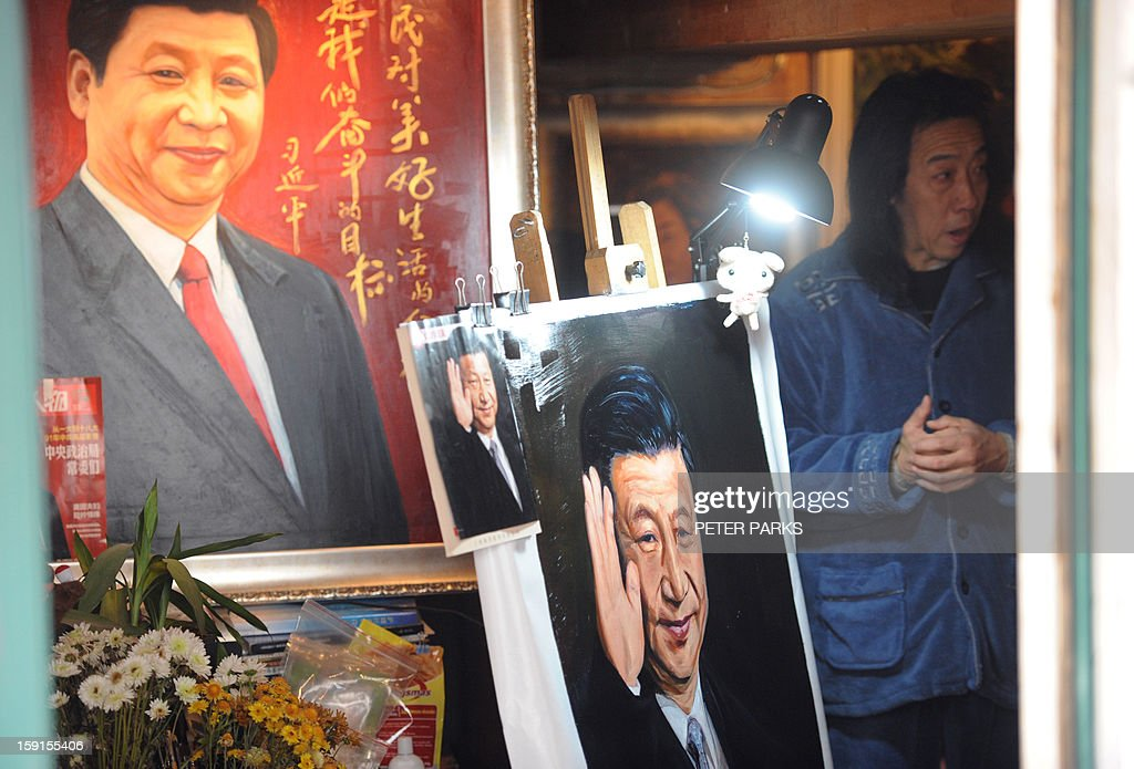 People look at paintings of China's President Xi Jingping (L) in a shop in Shanghai on January 9, 2013. China will overtake the United States economically within six years, the Nation's Health Report issued by the Chinese Academy of Sciences, an official research institute predicts, and go on to become the world's most important country in three decades more, state media said. AFP PHOTO / Peter PARKS